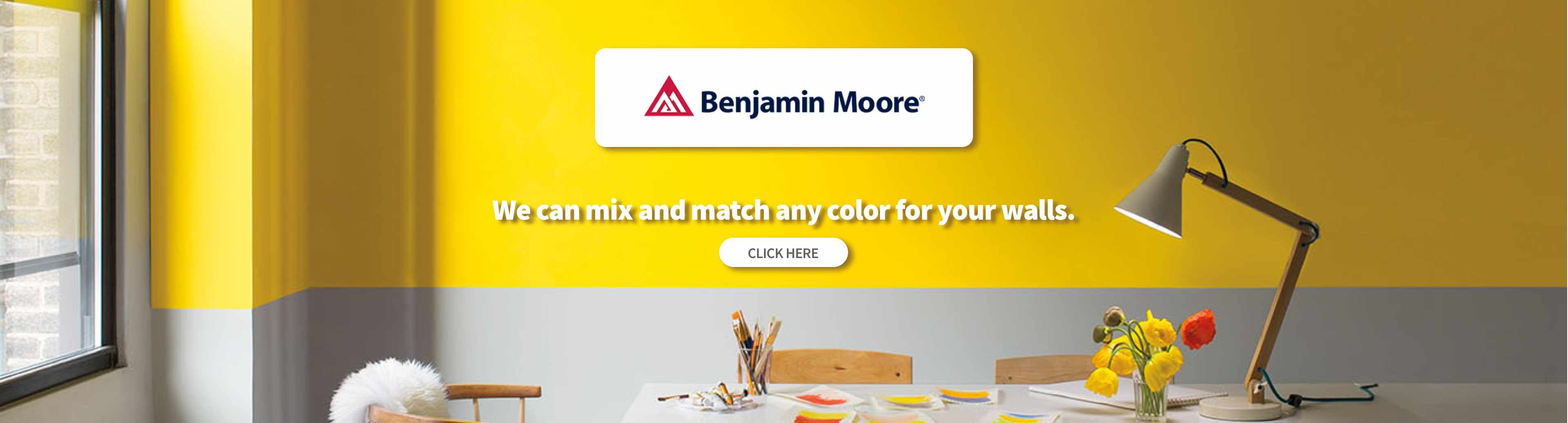 An minimalist type room is painted in Benjamin Moore bright yellow and light grey a table with art supplies and dead tuplips are lit by a trendy desk lamp.